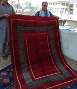 Didar Ali, head of workshop, holding recently finished Hunza carpet.