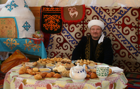 Kazakh in yurt with food for guests.